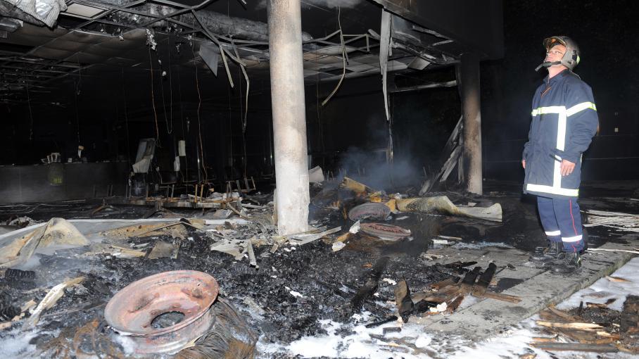 Un pompier inspecte les décombres du centre d'impôts de Morlaix (Finistère), incendié par des agriculteurs en colère, le 20 septembre 2014.