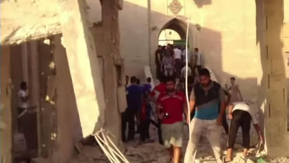 Capture d'écran d'un reportage montrant des Irakiens marchant dans les décombres du tombeau du prophèteJonas, détruit par l'Etat islamique le 24 juillet 2014, à Mossoul (Irak),