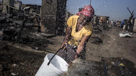 Une femme remplit un seau d'eau dans un bidonville en Afrique du Sud, le 10 octobre 2014.