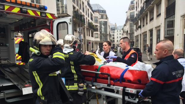 """Des pompiers évacuent un homme blessé devant les bureaux de """"Charlie Hebdo"""", ciblé par une attaque armée, le 7 janvier 2015 à Paris."""