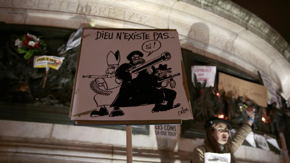 """Un manifestant brandit une caricature dessinée par Cabu, tué lors de l'attaque de """"Charlie Hebdo"""",lors du rassemblement du 7 janvier 2015, place de la République, à Paris."""
