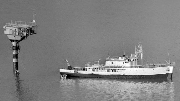 """La bouée-laboratoire du commandant Jacques-Yves Cousteau (à g.), permettant des observations sous-marines jusqu'à 50 mètres de profondeur, est remorquée par la """"Calypso"""", le 21 janvier 1964, près de Villefranche-sur-Mer (Alpes-Maritimes)."""