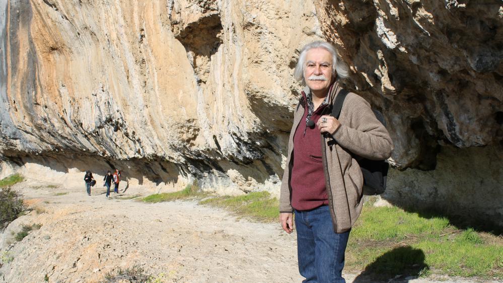 Jean-Michel Geneste, directeur de l'équipe scientifique de la grotte Chauvet, au bord de la falaise, à mi-chemin du sentier qui mène à la cavité de Vallon-Pont-d'Arc (Ardèche), le 18 mars 2015.