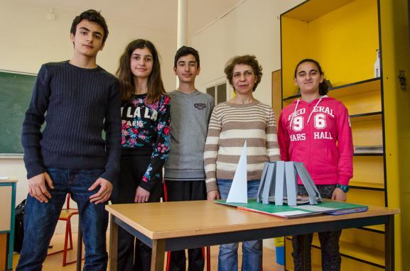 David, Chiara, Tatoul, leur professeurZepur Mehrabi et Marie posent devant une maquette du mémorial du génocide d'Erevan (Arménie), le 3 avril 2015 à l'école Tebrotzassère du Raincy (Seine-Saint-Denis).