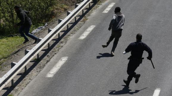 Un policier repousse des migrants aux abords de l'entrée du tunnel sous la Manche, le 21 mai 2015, à Calais.