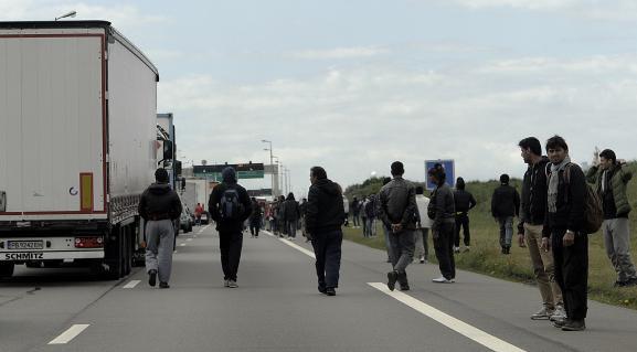 Des migrants profitent d'un embouteillage aux abords du port de Calais pour tenter de monter à bord de camions en partance pour l'Angleterre, le 20 mai 2015.