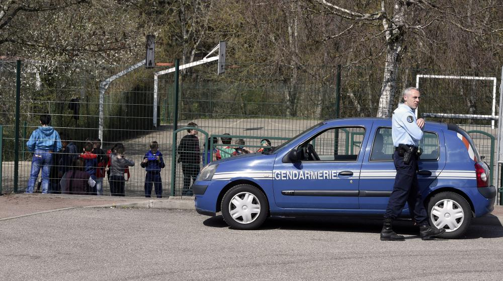Un gendarme est en poste devant l'école Le Mas de la Raz de Villefontaine (Isère), où un directeur d'école soupçonné de pédophilie a été arrêté, le 24 mars 2015.
