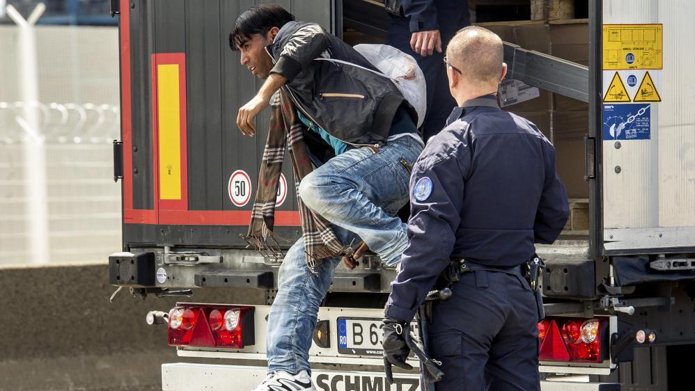 Un CRS fait descendre un migrant d'un camion, le 3 juin 2015 à Calais (Pas-de-Calais).