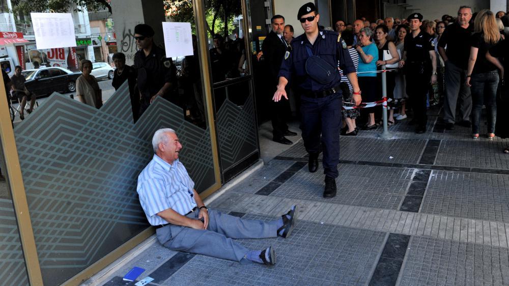Un retraité pleure assis sur le sol devant une banque, à Thessalonique, en Grèce.