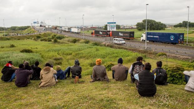 Des migrants patientent sur le bord de l'autoroute avant de tenter d'empruntrer le tunnel sous la Manche, à Calais, le 23 juin 2015.