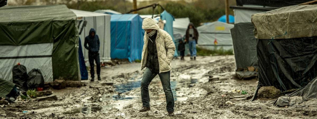 "Un migrant marche dans la ""jungle\"" de Calais, le 21 octobre 2015."