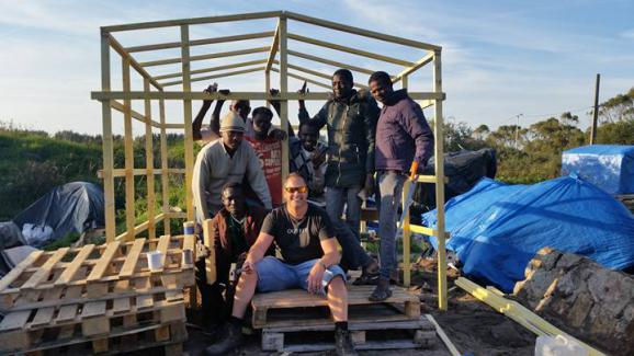 "Rob Lawrie pose devant un abri en construction, le 29 septembre 2015, avec des migrants, dans la ""jungle"" de Calais (Pas-de-Calais)."