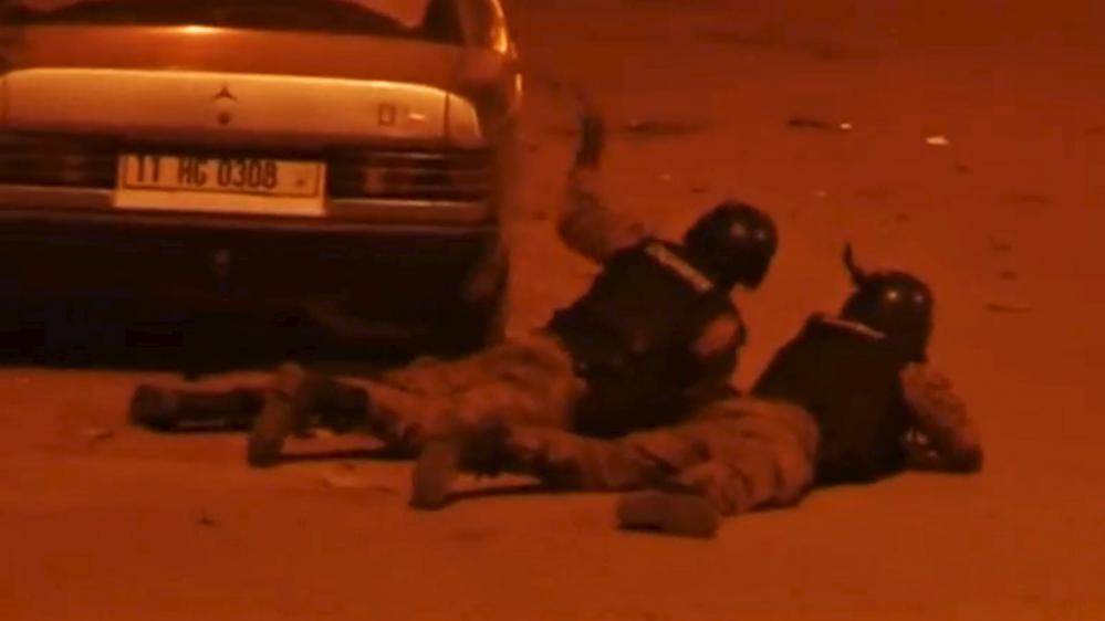 Des officiers de sécurité burkinabés couchés au sol pendant la prise d'otages à l'hôtel Splendid, à Ouagadougou, vendredi 15janvier.