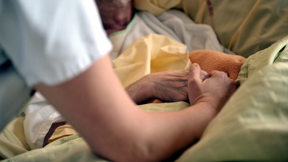 Une infirmière tient la main d'un patient dans une unité de soins palliatifs au centre hospitalier d'Auxerre (Yonne) le 11 février 2013.