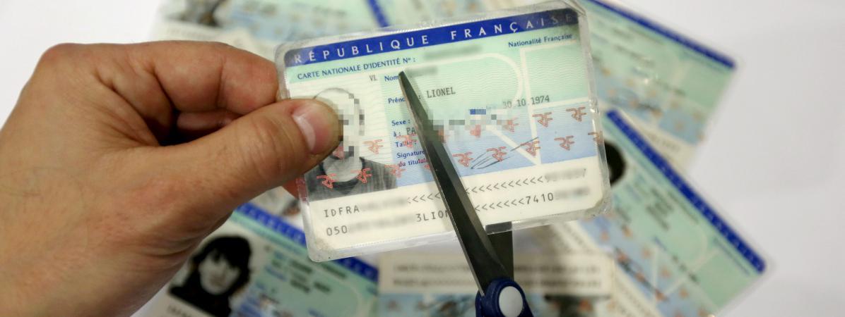 Un homme découpe une carte d'identité. (photo d'illustration)