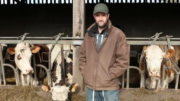 Christophe Gosselin devant les vaches laitières de son élevage à Fervaches (Manche) le 11 février 2016.