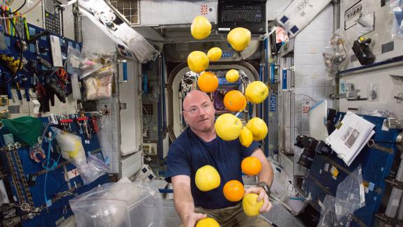 Scott Kelly jongle avec les fruits frais livrés par une navette cargo, le 25 août 2015, dans la Station spatiale internationale.