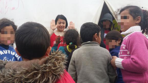 Une volontaire de l'ONG Save The Children joue avec des enfants au camp de migrants d'Idomeni (Grèe), le 16 mars 2016.