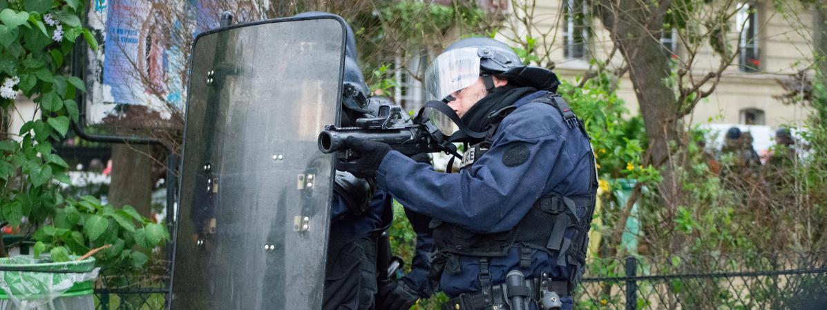 Un CRS pointe son arme sur des manifestants, le 12 mai 2016 à Paris.