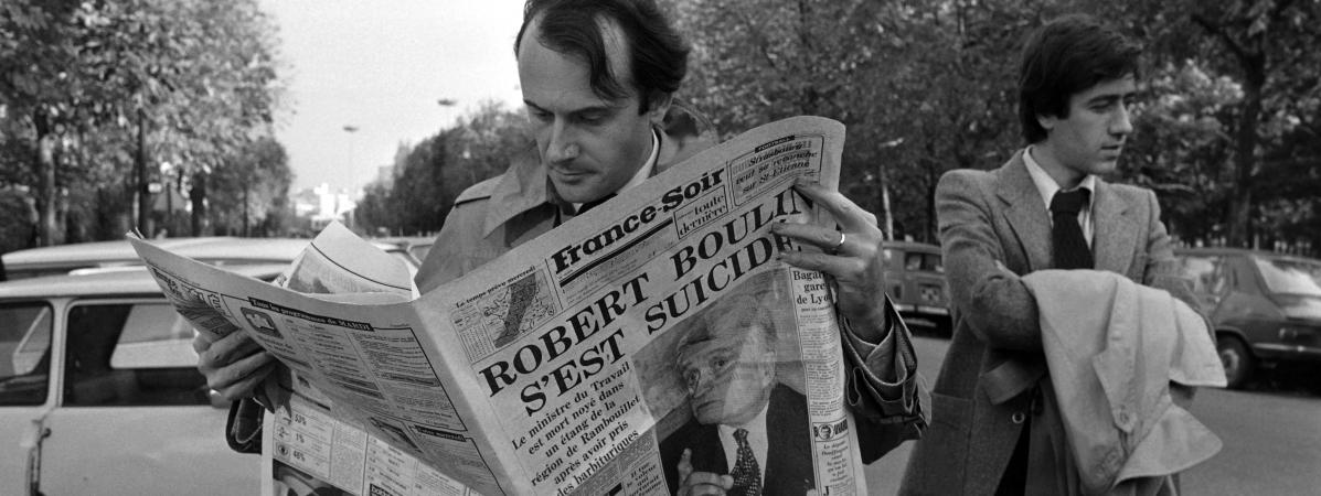 "Un homme lit le journal ""France Soir\"" qui évoque la mort de Roubert Boulin, à Paris, le 30 octobre 1979."
