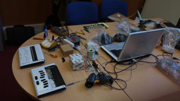 imagem 1: mesa com computador, linhas braille, ferramentas, muitos fios e grande confusão