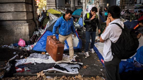 Un homme quitte la camp de migrants de Stalingrad avec sa valise, lundi 31 octobre 2016 à Paris.