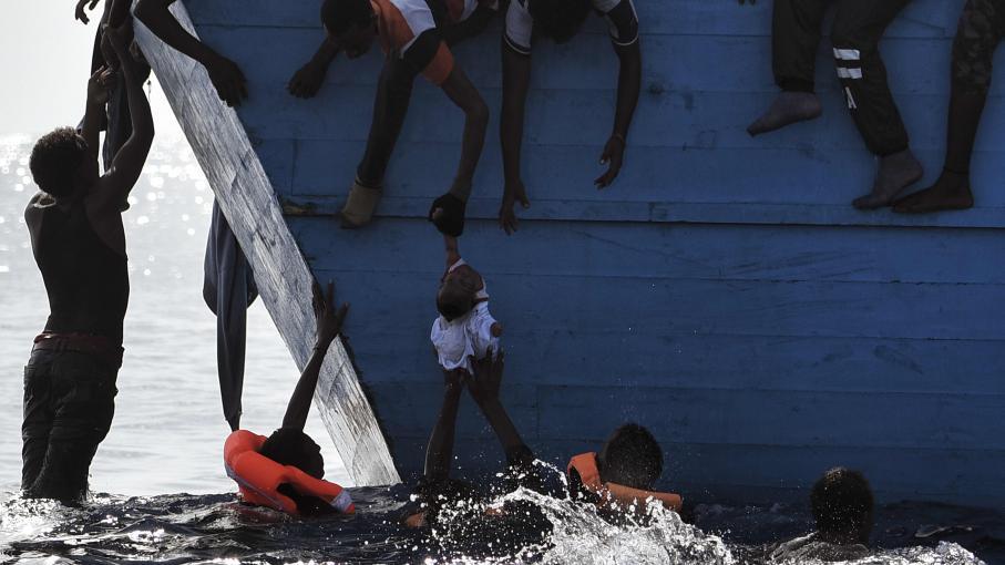 Des migrants tentent de protégerun enfant suspendu au-dessus de l\'eau au large des côtes libyennes, le 4 octobre 2016.