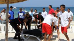 Des secouristes transportent un corps recouvert, vendredi 26 juin 2015 à Sousse (Tunisie). Au moins 37 personnes sont mortes dans une fusillade.