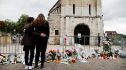 Des anonymes se recueillent devant l\'église de Saint-Etienne-du-Rouvray après l\'assassinat terroriste du Père Jacques Hamel, le 26 juillet 2016.