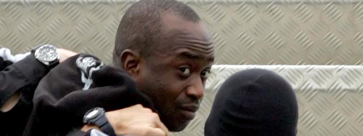 Youssouf Fofana est escorté par deux policiers pour le ramener à Paris en avion,le 4 mars 2006 à Abidjan (Côte-d\'Ivoire).