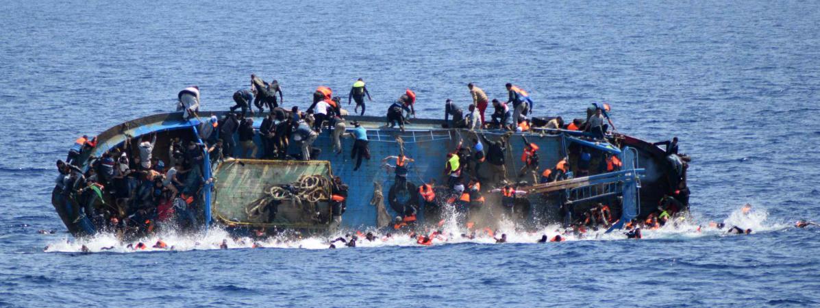 un artiste accroche la photo g ante du naufrage d 39 une barque de migrants au bord de la seine paris. Black Bedroom Furniture Sets. Home Design Ideas