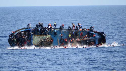 Un artiste accroche la photo géante du naufrage d'une barque de migrants au bord de la Seine à Paris