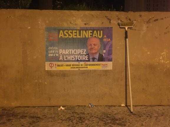 Une affiche de l\'UPR recouvre celles d\'un concurrent, le 29 mars 2017 à Paris.