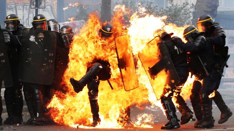 Des agents des forces de l'ordre visés par des cocktails molotov, à Paris, en marge du défilé du 1er-Mai, le 1er mai 2017. (ZAKARIA ABDELKAFI / AFP)