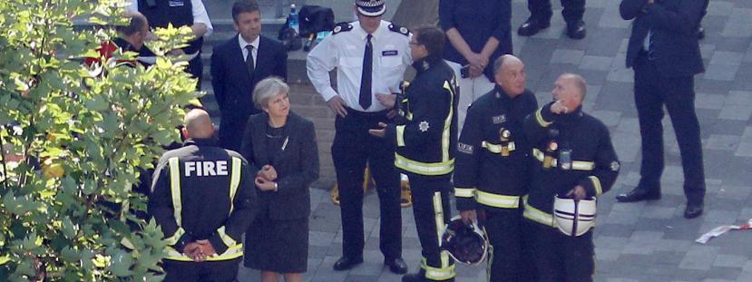 La Première ministre britannique Theresa May rencontre des secouristes, le 15 juin 2017, au pied de la Grenfell Tower, à Londres, dévastée par un incendie.