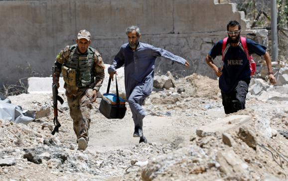 Un soldat irakien et des civils courent pour éviter les balles des snipers de l'Etat islamique, le 15 juin 2017, à Mossoul (Irak).