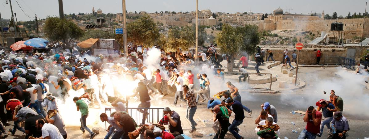 Des Palestiniens courent après des jets de gaz lacrymogène de la part des forces israéliennes, le 21 juillet 2017, dans une rue de Jérusalem.