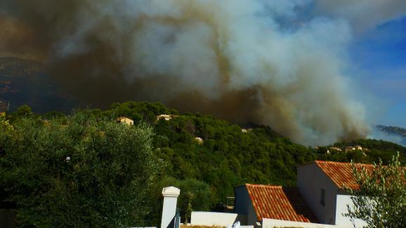 Des appareils luttent contre le feu à Carros (Alpes-Maritimes), lundi 24 juillet 2017, alors que le vent complique leur tâche.