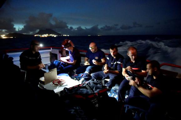 Des pompiers français à bord d\'un bateau se dirigeant vers l\'île de Saint-Martin depuis la Guadeloupe, le 8 septembre 2017, après le passage de l\'ouragan Irma.