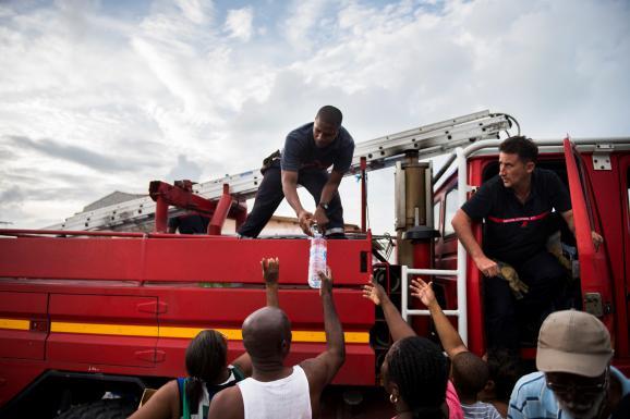 Après le passage de l\'ouragan Irma, des pompiers distribuent de l\'eauà des habitants du Marigot, le 10 septembre 2017, sur l\'île de Saint-Martin.