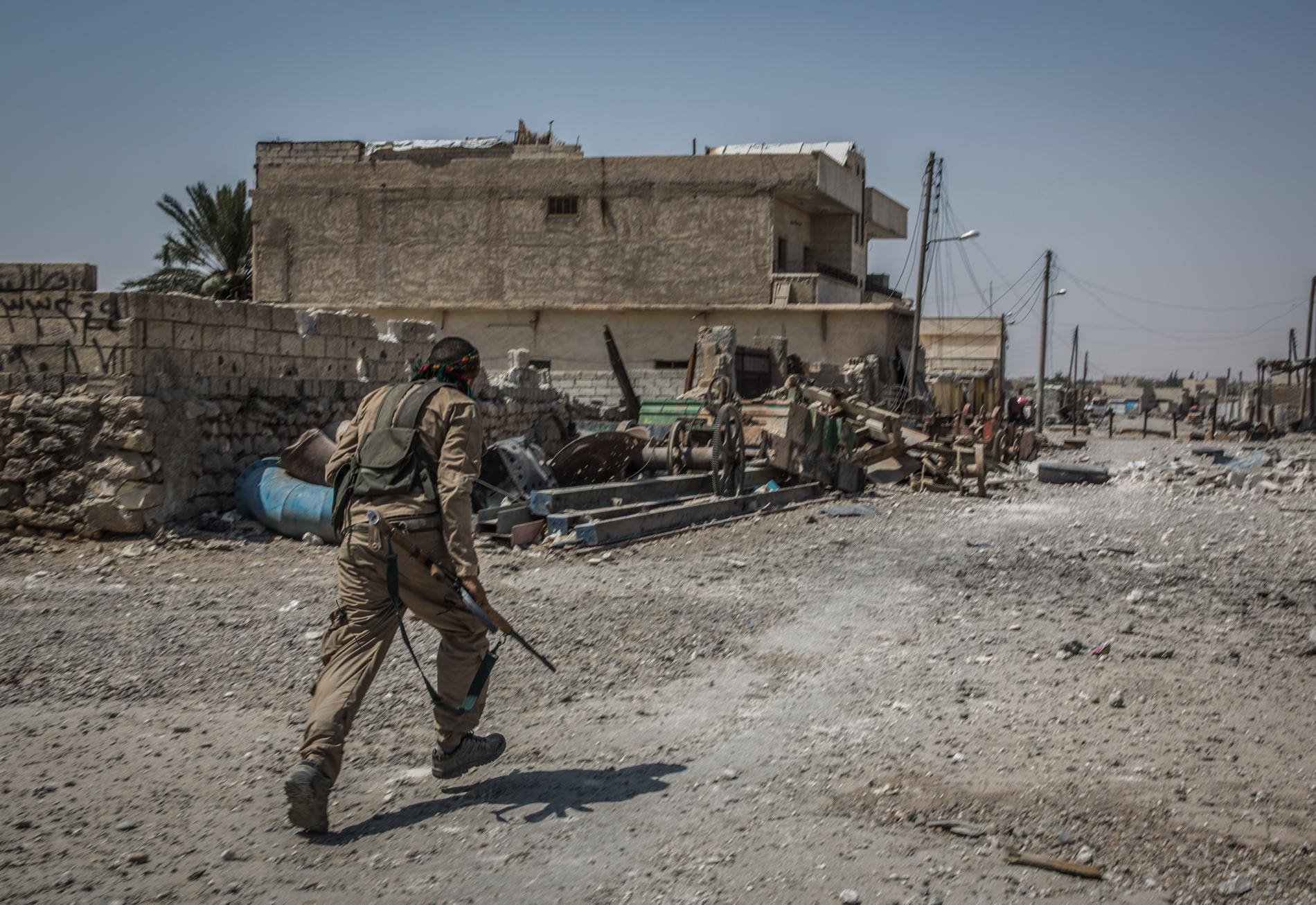 Un soldat des Forces démocratiques syriennes court dans une rue du quartier d'Al-Sinaa, à Raqqa (Syrie) pour tenter d'échapper à d'éventuels tirs de snipers.
