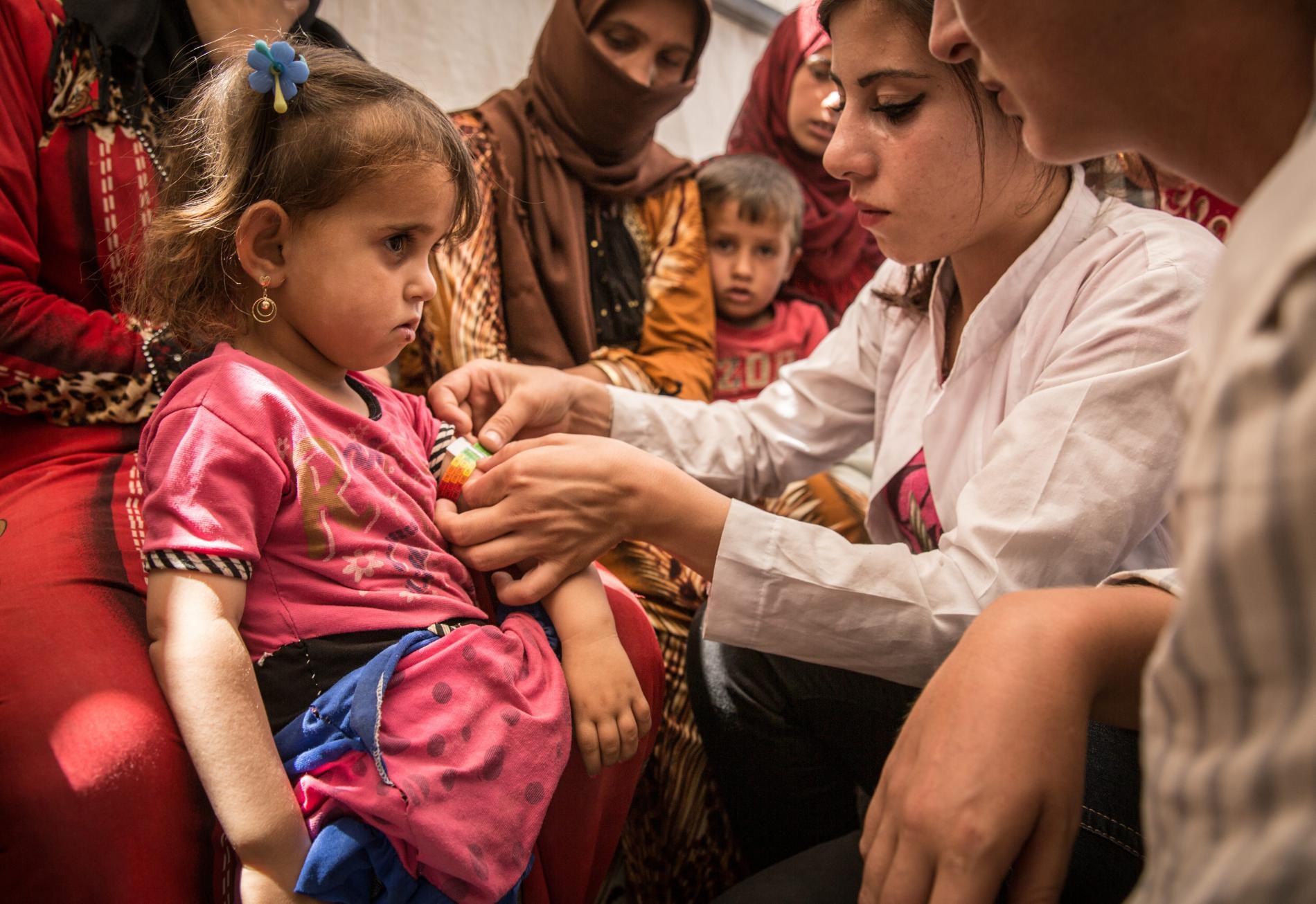 Dans le camp de réfugiés d'Ain Issa (Syrie), une médecin de l'ONG Médecins sans frontières ausculte une petite fille qui a fui Raqqa avec sa famille, le 8 juillet 2017.