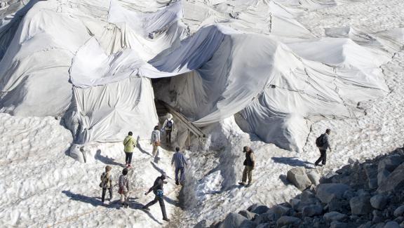 Des touristes visitent le glacier du Rhône (Suisse), protégé par des bâches blanches, le 19 juillet 2016.