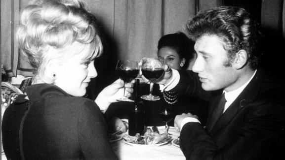 Sylvie Vartan trinque avec son compagnon Johnny Hallyday, le 15 juin 1964 dans un lieu non précisé.