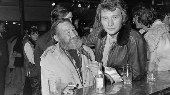 A l\'occasion de l\'inauguration de la brasserie du Bilboquet à Saint-Germain-des-Prés, à Paris, le 12 octobre 1970, Johnny Hallyday offre un verre à Mimile, un sans-abri du quartier.