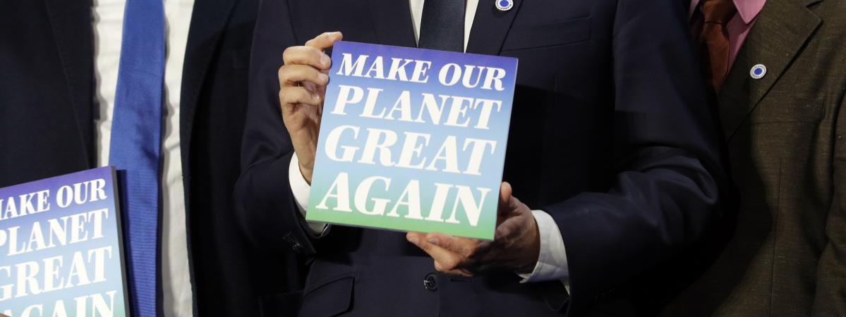 "Le président de la République, Emmanuel Macron, brandit un panneau ""Make our planet great again\"", le 11 décembre 2017 à Paris."