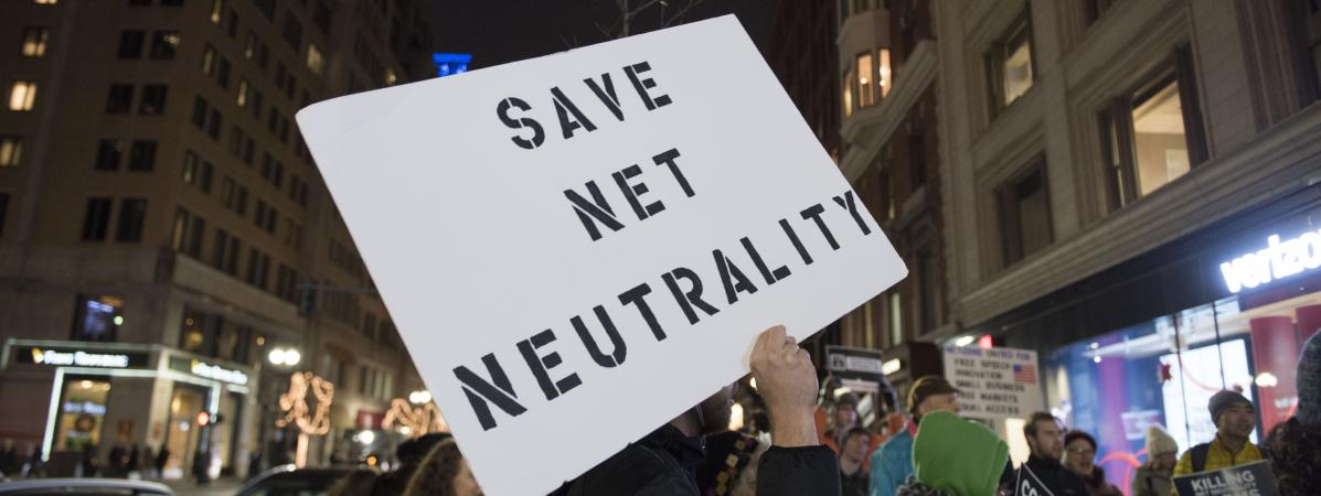 """Un manifestant avec une pancarte \""""sauvez la neutralité du Net\"""" à Boston, aux États-Unis, le 7 décembre 2017."""