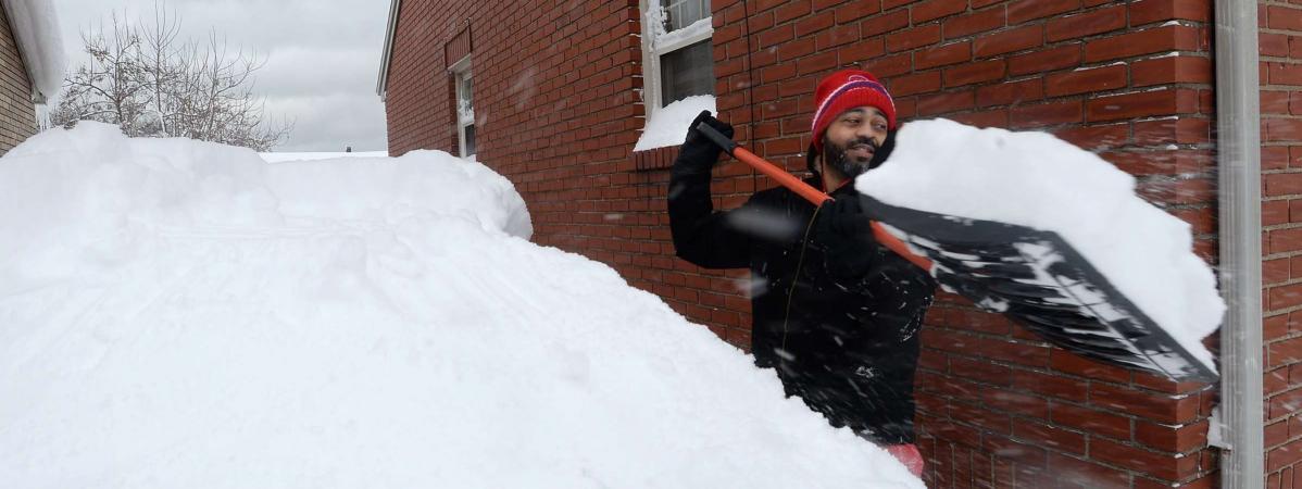 Un habitant d\'Erie (Pennsylvanie, Etats-Unis) déneige l\'accès à sa maison après des chutes de neige record dans cette ville, le 26 décembre 2017.