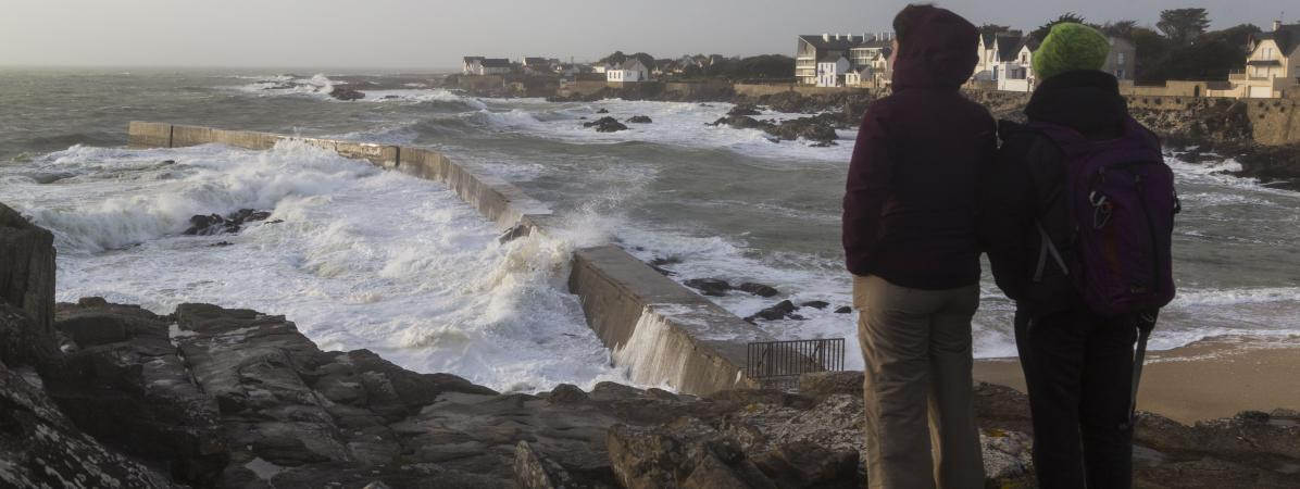 Deux promeneurs observent de fortes vagues s\'abattre sur une jetée au Croisic (Loire-Atlantique), le 30 décembre 2017.