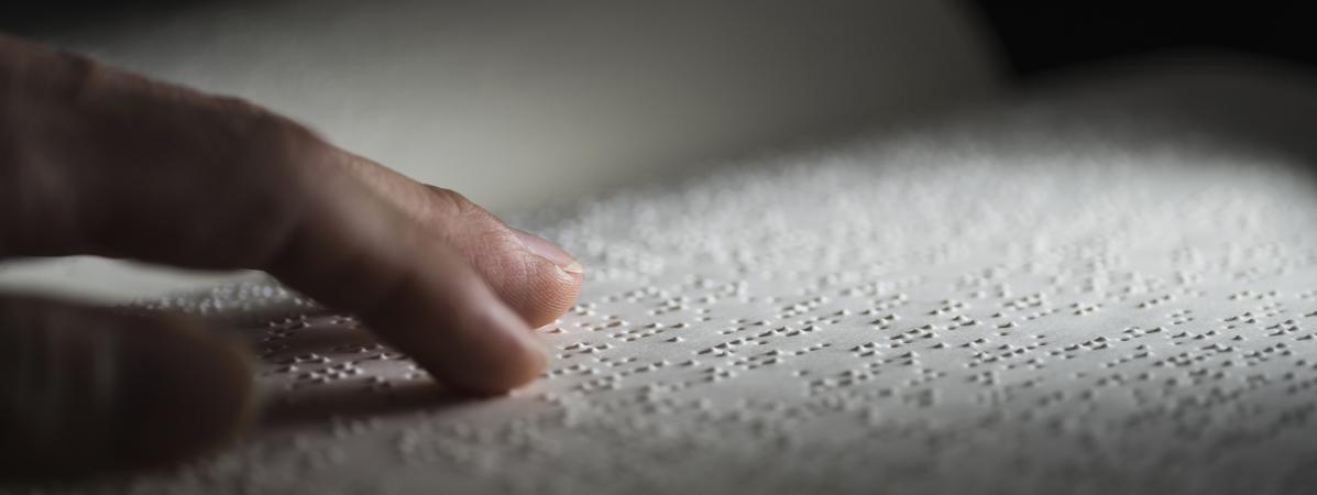 Une personne en train de lire un livre en braille.